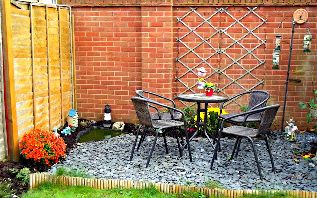 Stone chipping patio area with seating and a small pond.
