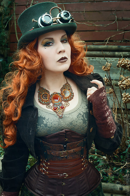 Steampunk redheaded woman wearing a top hat, goggles, necklace, corset, belt, jacket, lace top, arm warmers. Women's steampunk fashion