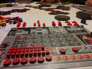 A view of the Eridani Empire play mat, with tokens on it representing being partway through a turn. The partially-constructed galactic map with player pieces on it can be seen beyond the player mat.