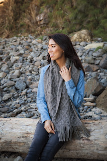 A woman sitting on a log, wearing a wide cabled scarf draped over her shoulders. The scarf comes down to just above her lap, and has fringe on the ends