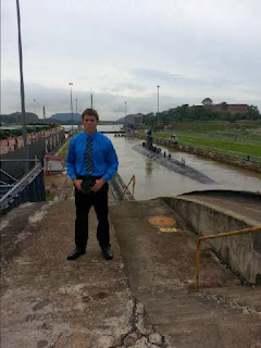 Intern Caleb Lenard poses with a submarine moving through the Panama Canal.