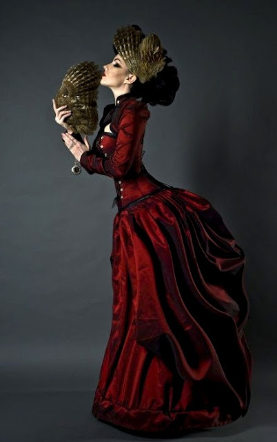 Women's neo-victorian clothing. Crimson red satin bustle dress (skirt, corset, bolero jacket). She wears a feather fascinator in her hair