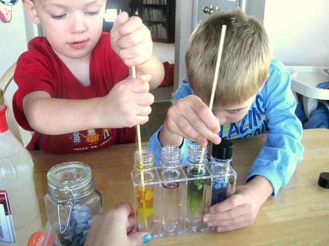 boys adding colored syrup to test tubes