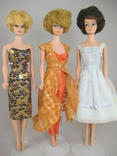 Three Barbies with bubble cut haircuts wearing gold lame dress, orange evening gown, gingham garden party dress
