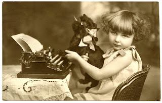 Vintage black and white image of a little girl and a plushy cat toy at a typewriter.