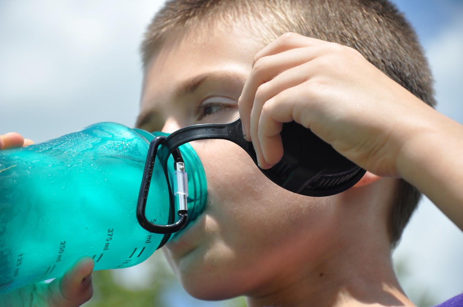 スポーツドリンクで喉の渇きを癒す少年