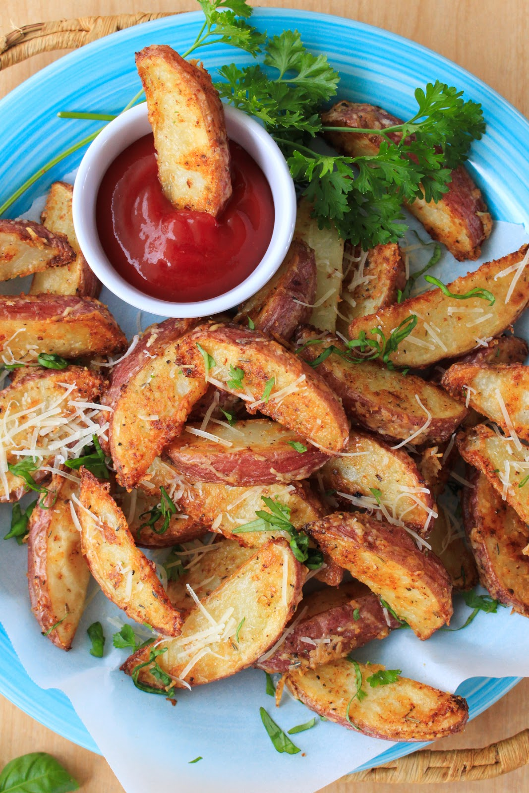 Parmesan Red Potato Wedges are coated with shredded parmesan cheese, herbs, and spices before baking in the oven until they are golden and crispy.  They are irresistible! #sidedish #potatoes