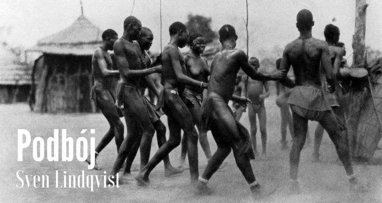 Czarnoskórzy mężczyźni w ludowych strojach tańczą w okręgu, w tle chatka; stara, czarno-biała fotografia