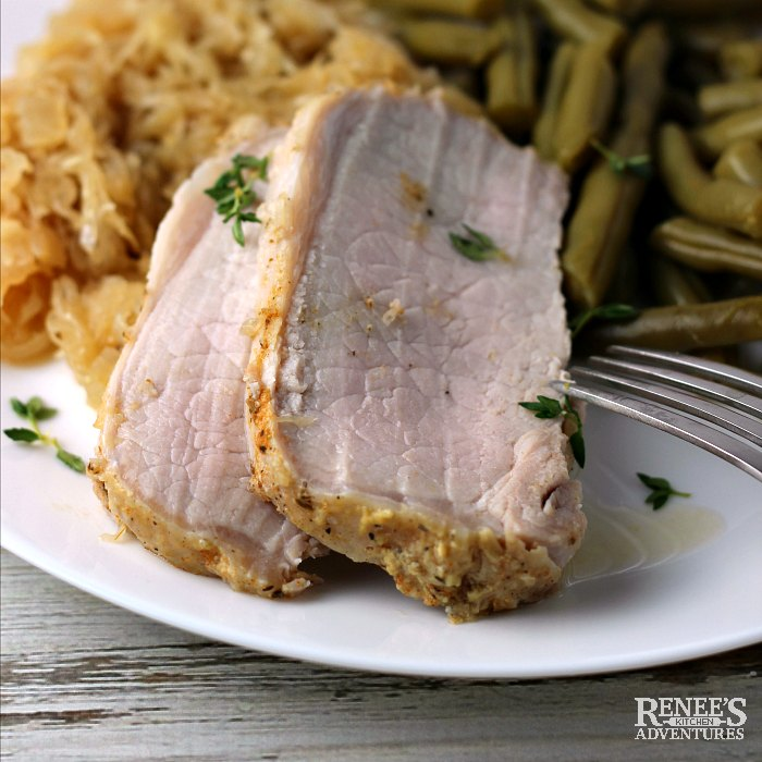 Pork Loin Roast carved into slices on plate with sauerkraut and green beans