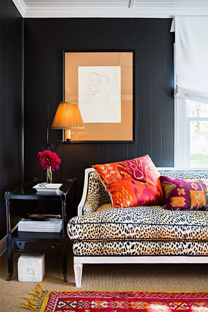 Black walls, leopard sofa, and pops of pumpkin orange - Fall decor inspiration