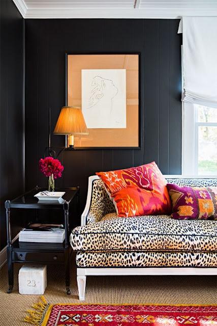 Black walls, leopard sofa, and pops of pumpkin orange - Fall decor inspiration