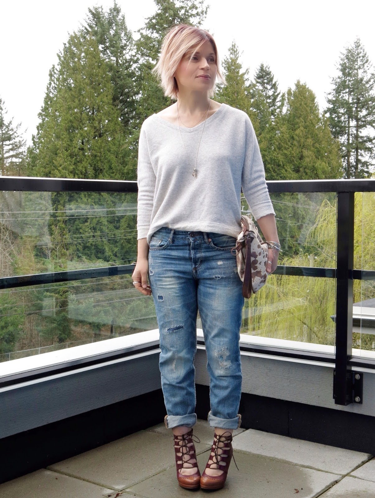 styling boyfriend jeans with a v-neck sweatshirt, pony hair bag, and lace-up heels