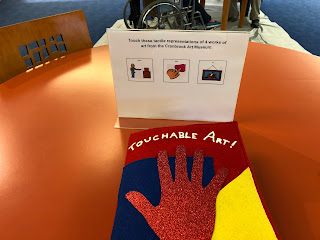 a sign with visuals and instructions to touch tactile representations of 4 works of art from the Cranbrook Art Museum is in front of a red flannel book that has a sparkly hand over a blue and yellow square background. The top of the book reads 'Touchable Art.'