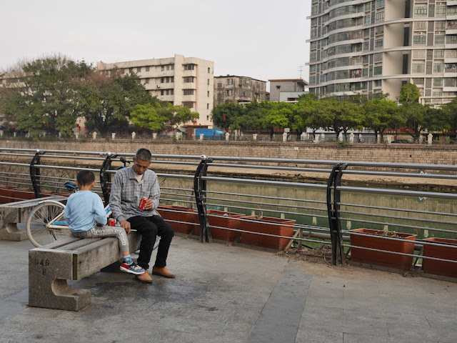 Man and boy sitting next to the Jiangmen River