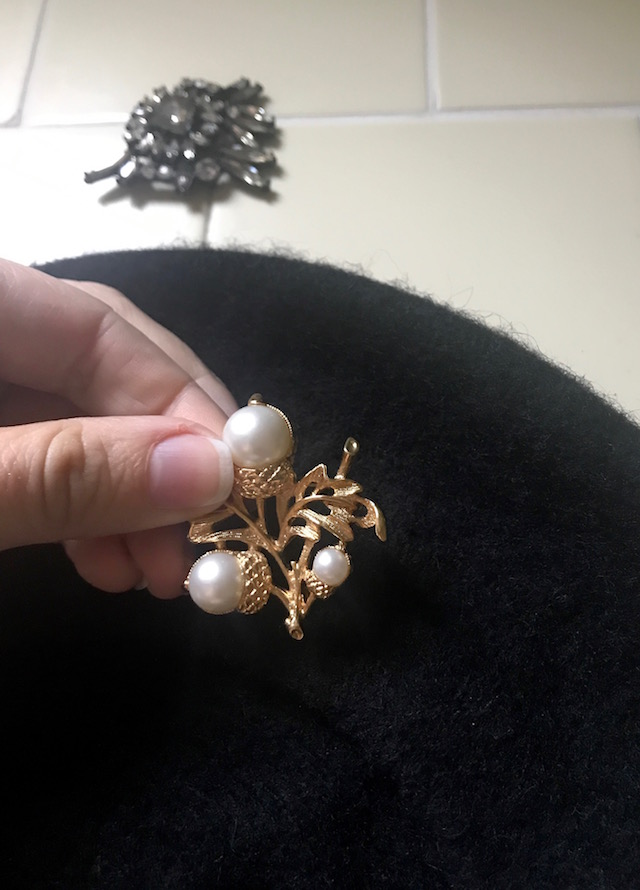 Placing new vintage brooch on beret