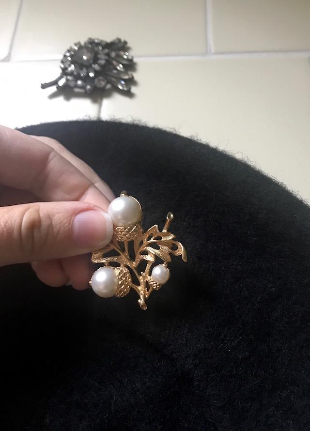 Placing new vintage brooch on beret
