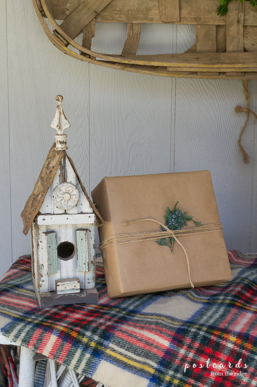 rustic vintage birdhouse on plaid blanket