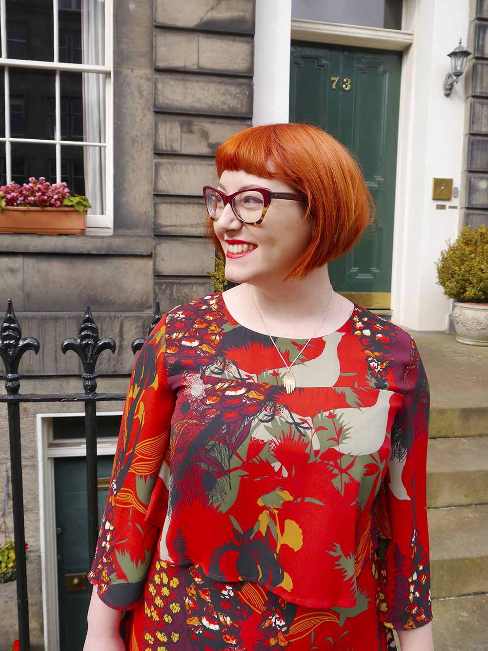Red haired Scottish blogger Helen from Wardrobe Conversations wear a frill layered Biba dress