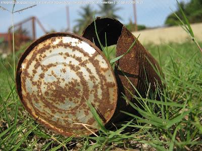 gambar sebuah tin susu buruk berkarat di atas tanah di atas rumput.