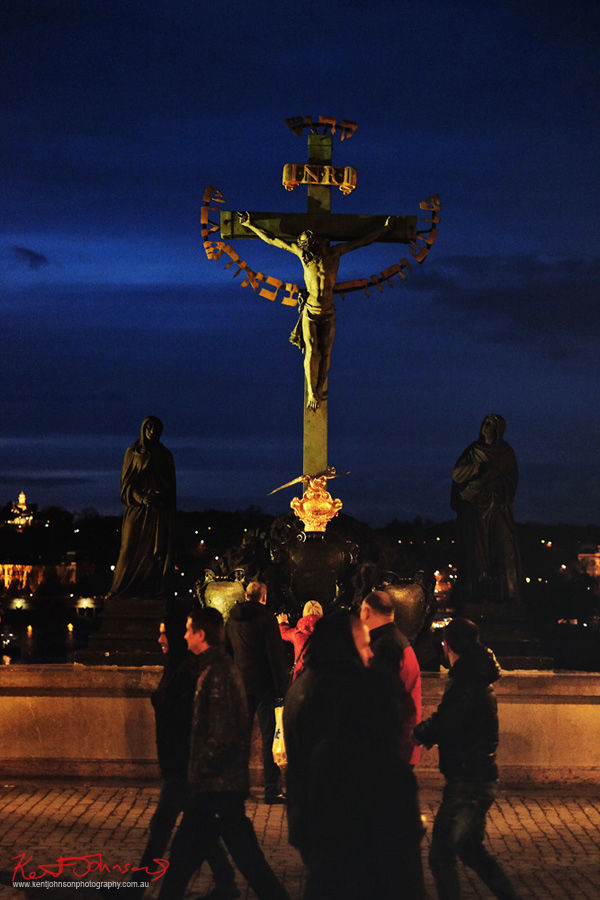 Statuary of the Holy Crucifix and Calvary - Woman rubbing the bronze of a statue of Jesus on the cross at night. The Charles Bridge in Spring Prague by Travel and Lifestyle Photographer Kent Johnson.