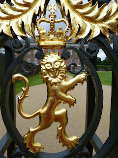 Close-up picture of a golden lion on a gate with an elegant building behind