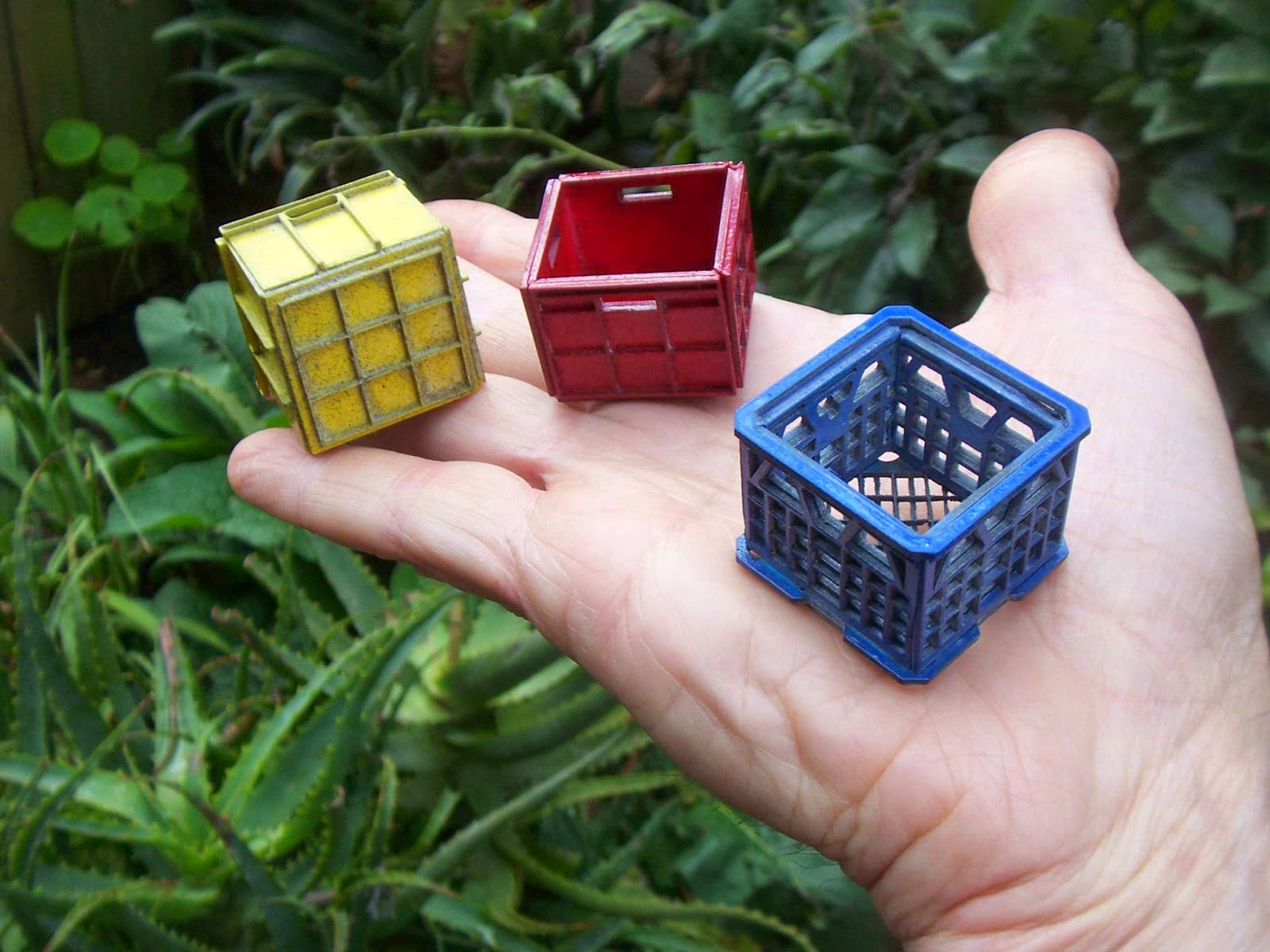 Three modern dolls' house miniature milk crates balanced on a hand.