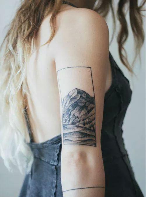 Chica de pelo rubio con vestido tejano, lleva en su brazo un tatuaje de paisaje