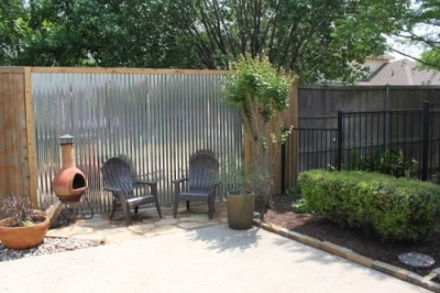 Lembaran seng pada pagar ini menciptakan aksen unik, selain untuk menciptakan privasi di halaman rumah.