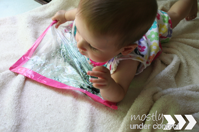 Baby playing with baby sensory water bag