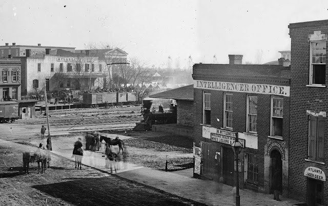 In Atlanta, Georgia, soldiers sit atop boxcars at a railroad depot. At right is the office of Atlanta's Daily Intelligencer newspaper. Panorama made from two photographs taken by George N. Barnard in 1864.
