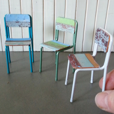Three one-twelfth scale miniature school chairs with frames painted in seafoam colours and seats and backs made of recycled wood pieces.