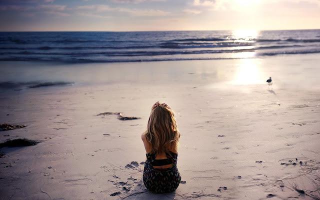 Foto met een vrouw op het strand kijkend naar een ondergaande zee