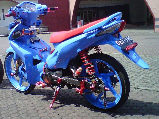 Foto Modifikasi Honda Revo Full warna di bagian seluruh bodi motor dibalut dengan airbrush warna biru muda termasuk juga pada lingkar pelek pun juga diubah warna biru untuk bagian jok tipis berwarna merah yang terlihat garang serta shocbreaker