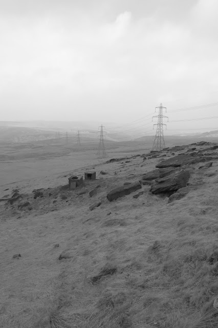 A chain of pylons disappearing into the hazy distance. Wicken Low is barely visible in the distance but gristone and ruined industrial buildings are in the foreground. (B&W)