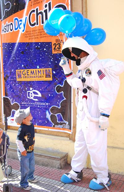 Niño pequeño observa a personaje vestido de astronauta