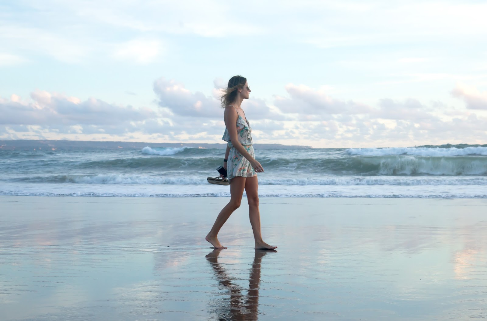 fashion and travel blogger, Alison Hutchinson, is wearing a Billabong Romper on the beach in Bali