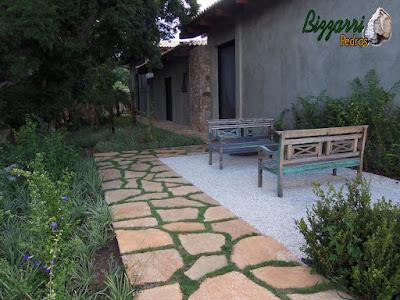Execução do caminho no jardim com cacão de pedra Goiás com juntas de grama na praça com os bancos de madeira, o piso de pedrisco palha e execução do paisagismo em residência em Piracaia.