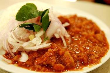 Foto de un plato de carapulcra con ensalada de cebolla