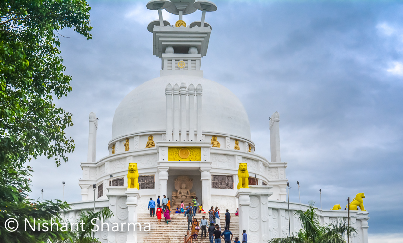 This beautiful Shanti Stupa is located around Dhauli which is on the banks of Daya river and place is about 8 km away from Bhubaneshwar. There are lot of stories associated with Dhauli Hills and how Ashoka is connected with this region. Dhauli has more to offer apart from this Shanti Stupa.This white peace pagoda is built by Japan Buddha Sangha and Kalinga Buddha Nippon Buddha Sanga.Dhauli is near major edicts of Ashoka, which are engraved on a huge rock which is preserved. Ashoka shares about welfare of the whole worlds on this rock. There is a rock cut elephant above these edicts which is considered as earliest buddhist sculpture of Odisha.It seems that Kalinga war happened around Dhauli hills. It seems that Ashoka realized the horror of a war when he noticed red Daya river with the blood of people after battle. He built various stupas and pillars around this place.This Stupa is located on a high hill which offers great views of surroundings. And Monsoons made it special for us. Everything looked fresh and green. Cloud play made the day best for photographing this place in better way. Daya river looks amazing, especially in Monsoons.Stay tuned for more exciting Photo Journeys from Bubaneshwar, Odisha.