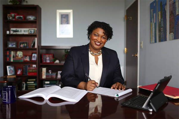 image of Stacey Abrams, a Black woman, sitting at a desk, writing on a notepad