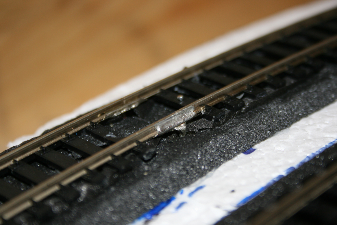 Installed metal track terminal connectors with soldered power leads leading below foam roadbed