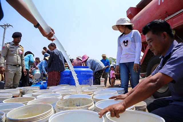Authorities distribute water from a fire truck into buckets late last month in Banteay Meanchey province during water shortages. Photo supplied
