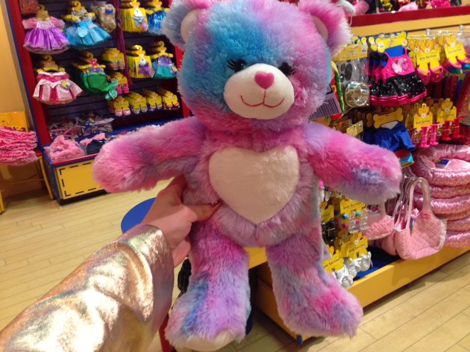 the multicoloured bear I made at the bear factory. its fur it mostly pink with hints of blue and purple throughout