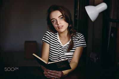 Preciosa chica leyendo un libro en su habitación oscura