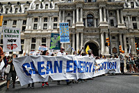 Climate change activists carry signs as they march during a protest in downtown Philadelphia in July. (Credit: John Minchillo/AP) Click to Enlarge.