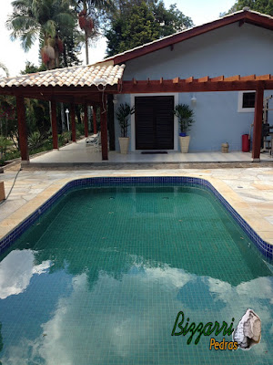 Construção de piscina em residência em condomínio em Atibaia-SP com o piso de pedra São Tomé e o pergolado de madeira.
