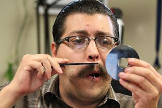 uomo che si pettina i baffi specchiandosi su un CD