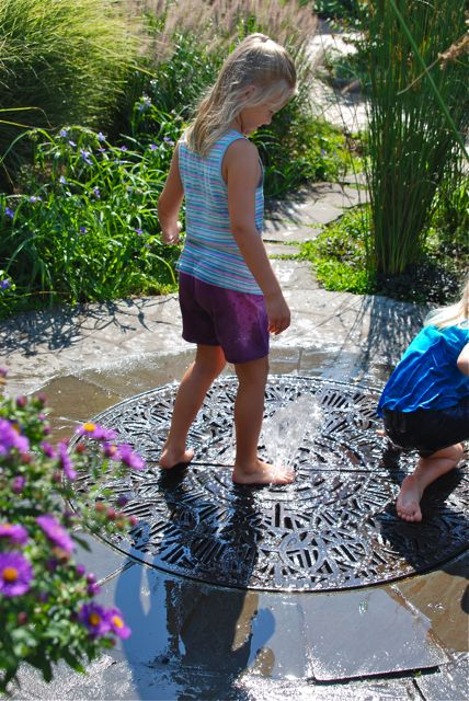 Grace stepping on the bubbling fountain in the middle of a decorative metal grate. My kids love to play with this small, simple water feature for hours! I think it would be a fun design to include in a home garden.