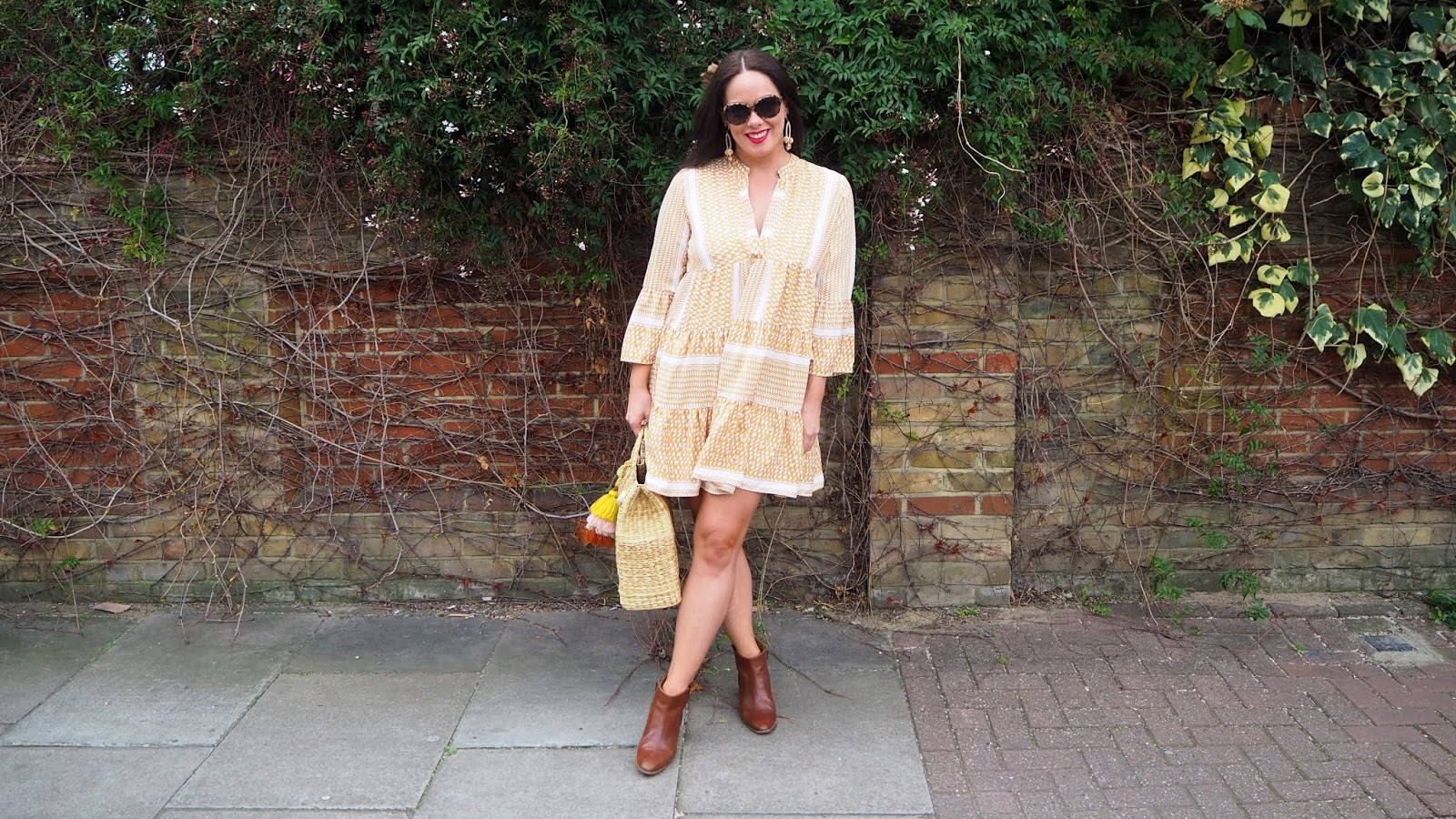 Yellow and white print smocked dress with brown boots and straw bag