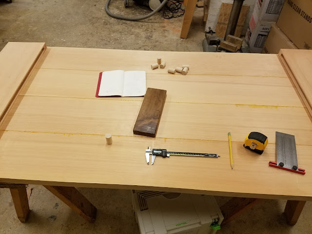 a photo of the tabletop on sawhorses, with dowel plugs, measuring tools, and a notebook scattered on top.
